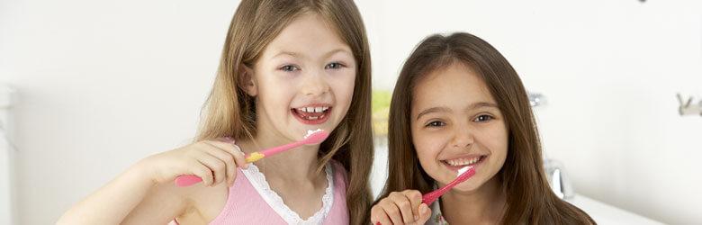 Two girls brushing their teeth