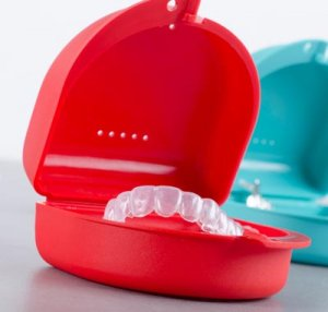 teeth whitening trays in red and blue cases