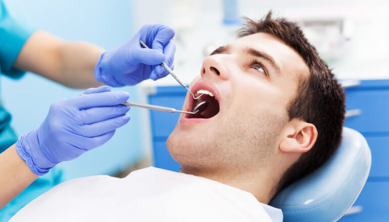 Brunette man getting his teeth cleaned at the dentist by a hygienist in blue gloves