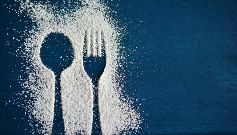 A silhouette of a fork and spoon in powdered sugar on a blue counter