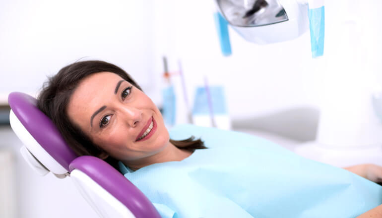Brunette lady in dental chair awaiting root canal therapy