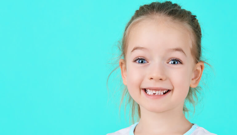 Smiling girl on a bright mint colored background with a missing baby tooth on the bottom