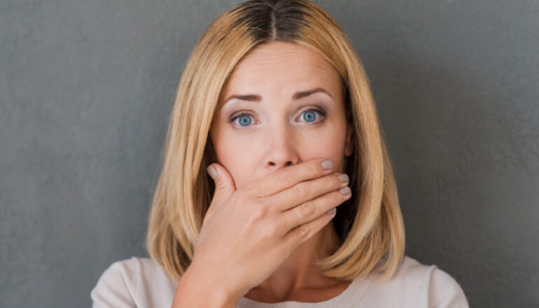 woman covering her mouth with her hand to hide yellow teeth