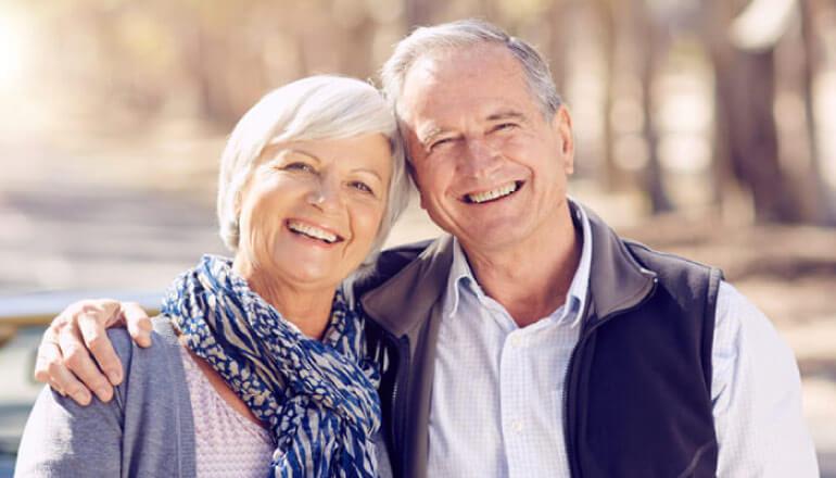 senior couple hug and smile after getting dental crowns