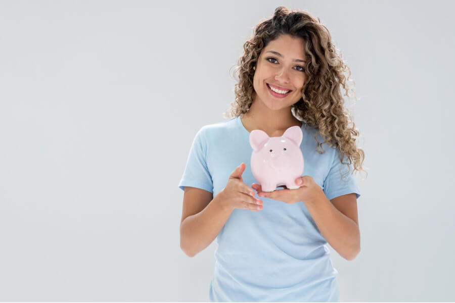 young woman holds a pink piggybank and smiles because of affordable dentistry