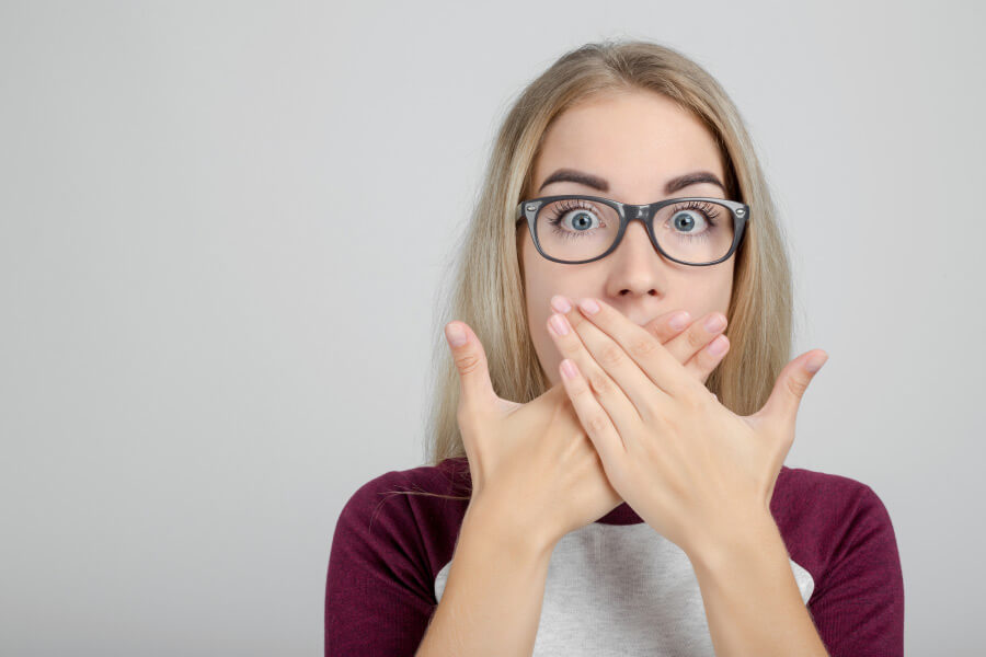 young woman wearing glasses covers her mouth with both hands to hide bad breath